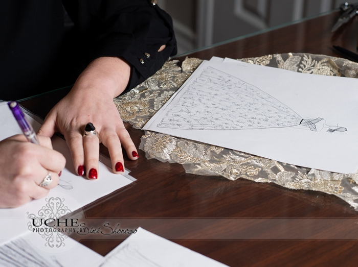 05_Ashley draws a new custom wedding dress design at her desk at A.Cherie Couture studio beside a completed ballgown wedding dress on top of some gold lace